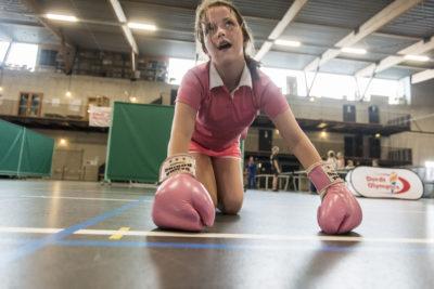 Nederland, Dordrecht, 23-06-2016 Sportbedrijf Dordtsport organiseert jaarlijks een Dordt Olympics voor basisschoolleerlingen. De kinderen krijgen een assortiment aan sporten aangeboden vanuit de gemeente. Het doel is kinderen meer te laten bewegen en kennis te laten nemen van het aanbod aan sport, in de hoop dat ze er zelf gebruik van gaan maken. Meisje steunt met haar handen in bokshandschoenen, uitgeput op de grond, bezweet foto: ©Ronald van den Heerik/Hollandse Hoogte